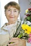Bejaarde met bloemen Stock Fotografie