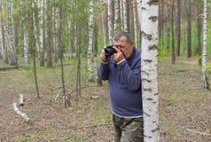 Bejaarde met camera die zich dichtbij berk bevinden Stock Afbeelding