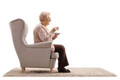 Bejaarde met een kop gezet in een leunstoel stock afbeeldingen