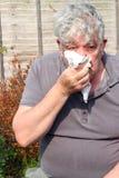 Bejaarde met een koude. Royalty-vrije Stock Afbeelding