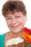 Bejaarde met gerberas stock afbeelding