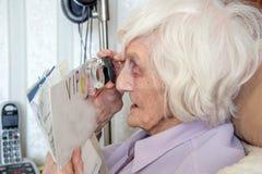 Bejaarde met gezichtsstoornissen met het overdrijven loupe royalty-vrije stock foto