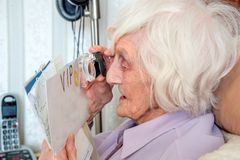 Bejaarde met gezichtsstoornissen met het overdrijven loupe stock foto's