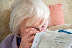 Bejaarde met gezichtsstoornissen met magnifyer royalty-vrije stock fotografie
