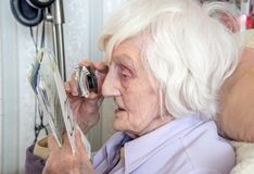 Bejaarde met gezichtsstoornissen met magnifyer royalty-vrije stock foto
