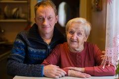 Bejaarde met haar volwassen kleinzoon stock foto