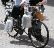 bejaarde met oude fiets en melkblikken Stock Afbeelding