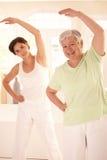 Bejaarde met persoonlijke geschiktheidstrainer Stock Foto