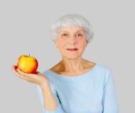 Bejaarde met rode appel in handen op een lichte achtergrond royalty-vrije stock foto