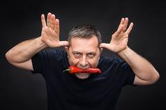 Bejaarde met Spaanse peper in zijn mond Stock Foto's