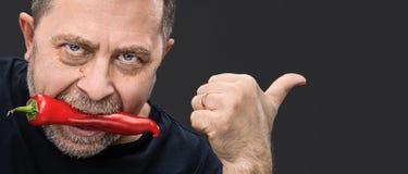 Bejaarde met Spaanse peper in zijn mond Royalty-vrije Stock Foto's