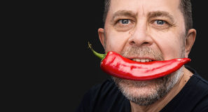 Bejaarde met Spaanse peper in zijn mond Royalty-vrije Stock Foto