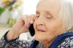 Bejaarde met telefoon stock foto