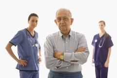 Bejaarde met verpleegsters Stock Foto's