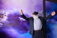 Bejaarde moderne mens gebruikend VR-onderhouden glazen en uit hangend royalty-vrije stock fotografie