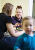 Bejaarde moeder en dochter die van een maaltijd genieten stock foto