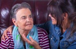 Bejaarde moeder en het volwassen dochter glimlachen royalty-vrije stock afbeeldingen
