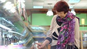 Bejaarde mooie vrouw die voor vers gezond voedsel in de supermarkt winkelen stock video
