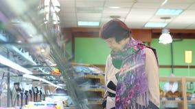 Bejaarde mooie vrouw die voor vers gezond voedsel in de supermarkt winkelen stock footage