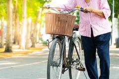 Bejaarde Oefening: De oude vrouwen berijden een zwarte fiets op stre stock foto's