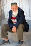 Bejaarde Oezbekistaanse zitting op een rots Stock Foto's