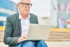 Bejaarde ondernemer die aan muziek luisteren en laptop met behulp van royalty-vrije stock foto