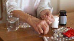 Bejaarde onherkenbare vrouw die een dagelijkse dosis pillen met een glas water drinken De handen van een persoon met artritis stock videobeelden