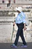 Bejaarde oude turistvrouw die met stok in Rome (Italië) lopen Stock Afbeelding