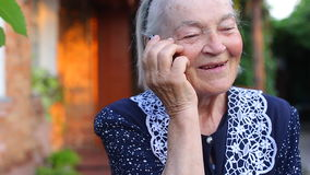 Bejaarde oudere vrouwelijke vrouw die bij telefoon het smilling spreekt stock footage