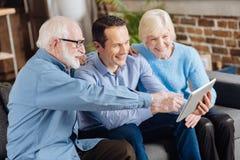 Bejaarde ouders die hun zoonsvragen stellen over tablet royalty-vrije stock afbeeldingen