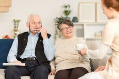 Bejaarde paar en verpleegster stock foto's