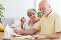 Bejaarde paar het berekenen kosten van huishouden De hogere mensen weten royalty-vrije stock foto's
