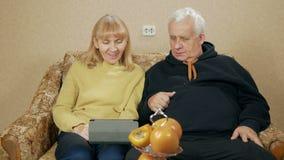 Bejaarde paarringen op de videoverbindingen op de tablet Echtgenoot en vrouwenzitting thuis op de laag Het concept van stock footage