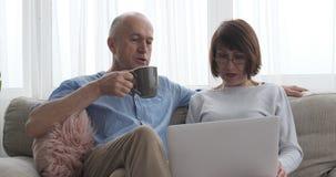 Bejaarde paarzitting met laptop en kop van koffie thuis stock videobeelden