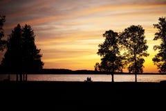 Bejaarde paarzitting op een bank door meer bij sunse Royalty-vrije Stock Fotografie