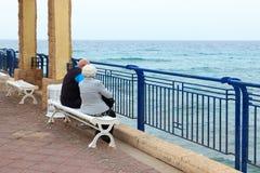Bejaarde paarzitting op het overzees stock afbeelding