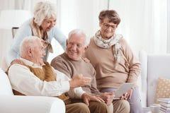 Bejaarde paren die technologie gebruiken stock fotografie