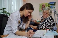 Bejaarde patiënt bij een verpleegsters` s benoeming stock afbeeldingen
