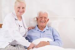 Bejaarde patiënt die in bed terugkrijgen stock afbeelding