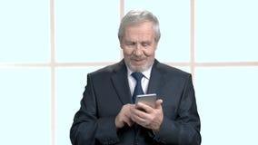 Bejaarde persoon in formele slijtage met smartphone stock videobeelden
