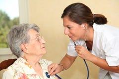 Bejaarde persoon met verpleegster thuis Stock Foto