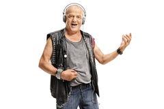 Bejaarde punker die hoofdtelefoons dragen en luchtgitaar spelen Stock Foto