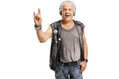 Bejaarde punker die met hoofdtelefoons een gebaar van de rotshand maken stock foto's