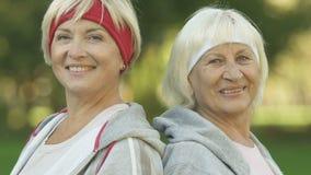 Bejaarde sportenvrouwen die duimen, actieve levensstijl, energie en sterkte tonen stock video