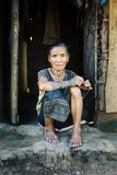 bejaarde stammenvrouw met traditionele tatoegeringen voor haar huis royalty-vrije stock fotografie