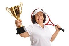 Bejaarde tennisspeler met een gouden trofee en een racket Stock Fotografie