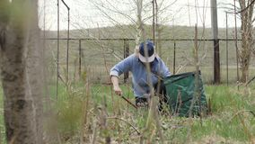 Bejaarde tuinmanvrouw die in tuinbinnenplaats werken Het seizoengebonden schoonmaken in tuin stock footage