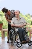 Bejaarde uit voor gang in rolstoel stock foto