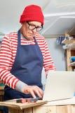 Bejaarde vakman die laptop met behulp van stock afbeeldingen