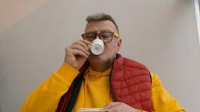 Bejaarde van Kaukasische nationaliteit, in heldere kleren, het drinken koffie stock footage